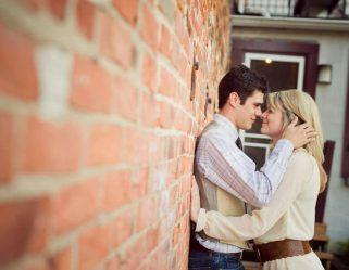 Couple embracing against brick wall