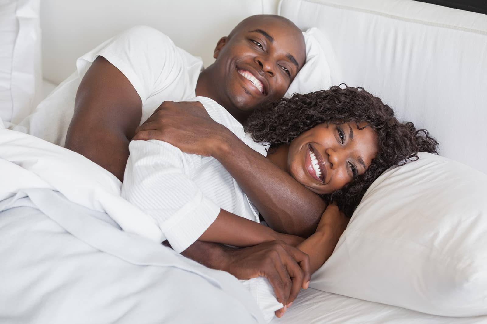 black couple hugging and laughing in bed